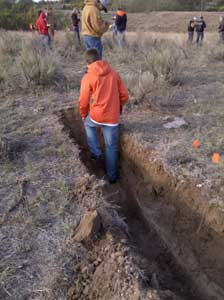 Contestant exiting shallow narrow pit in field.