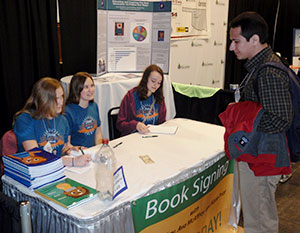 image of students signing book copies