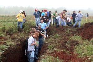 image of contestants examining soil