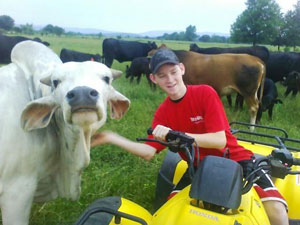 image of boy on tractor posing next to an animal